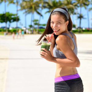 woman walking on pier sipping green juice and smiling
