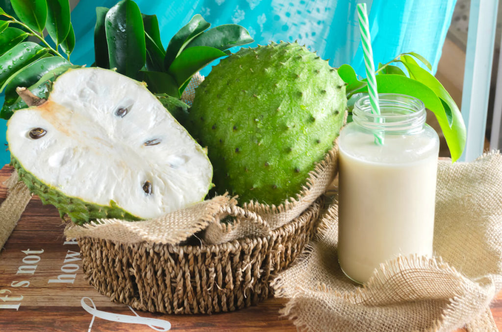 freshly cut soursop next to a glass of soursop juice