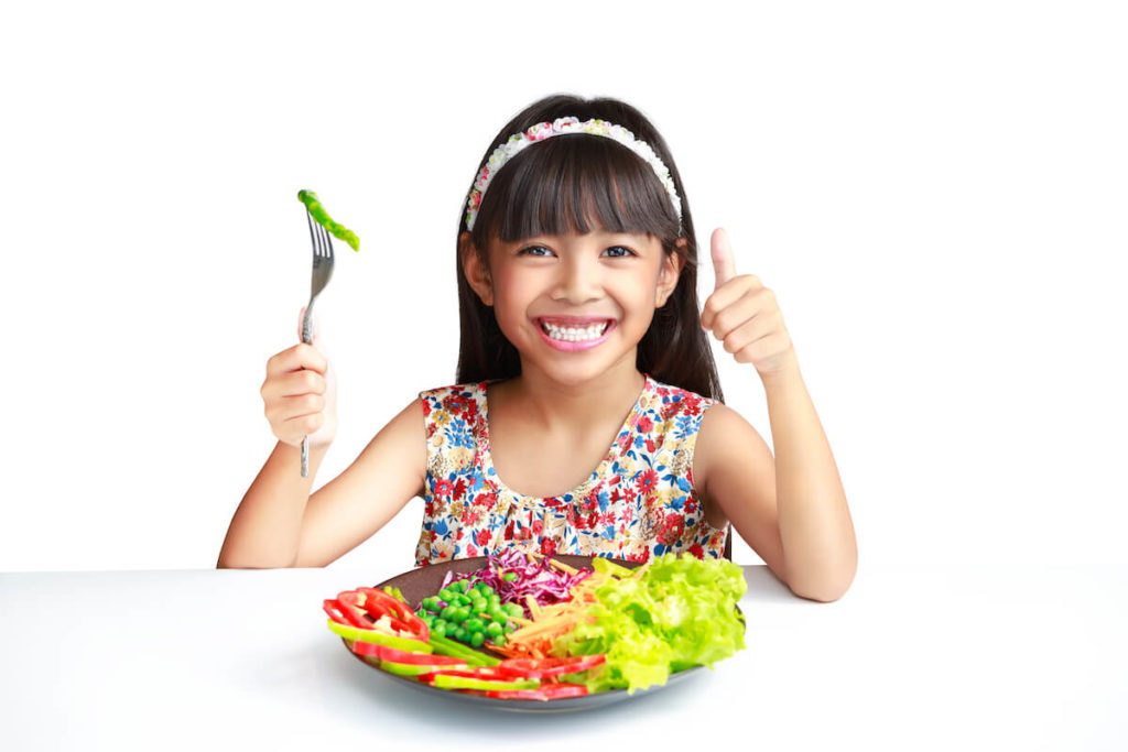 kid giving the thumbs up over a plate of fresh vegetables