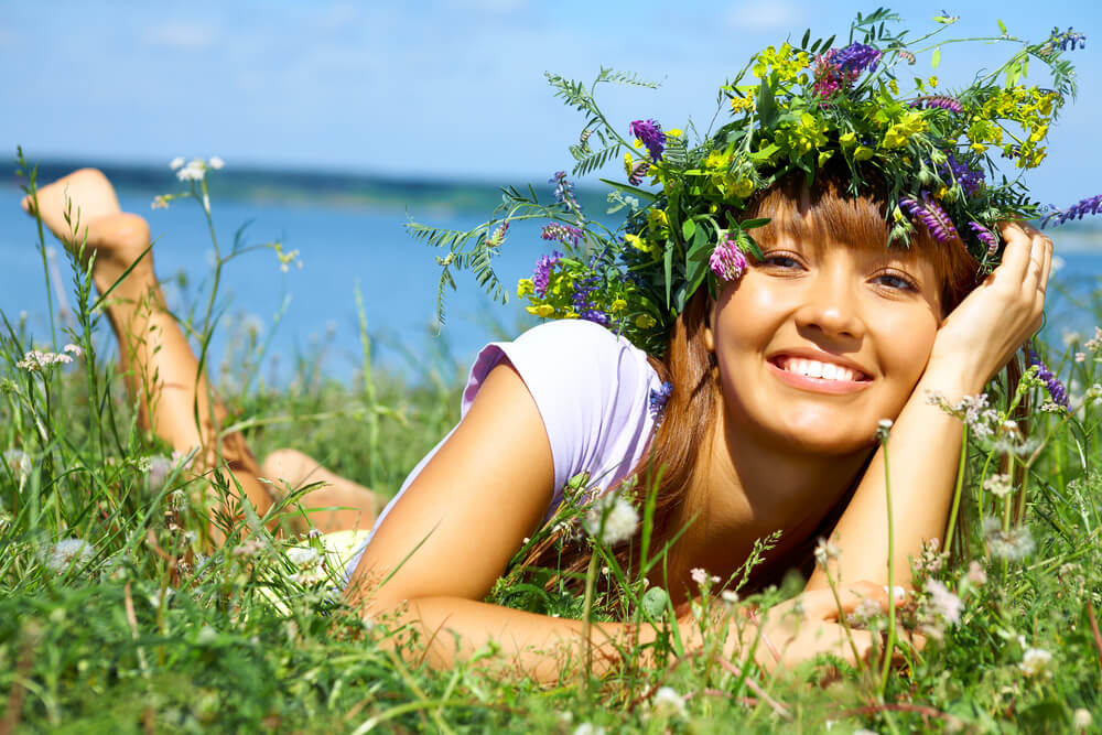 woman with flower crown on field, smiling and happy