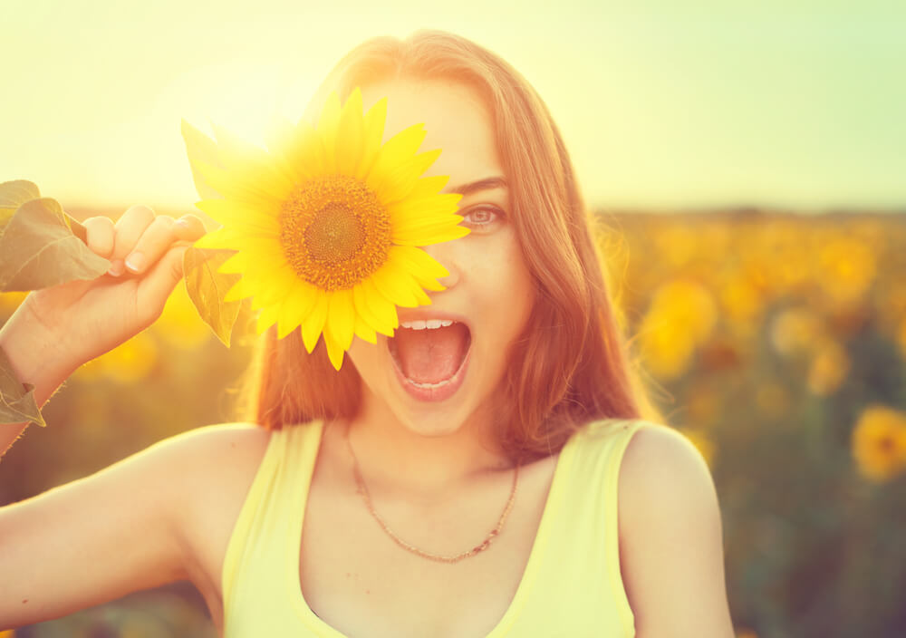 teenage girl with sunflower enjoying nature and laughing on summer sunflower field