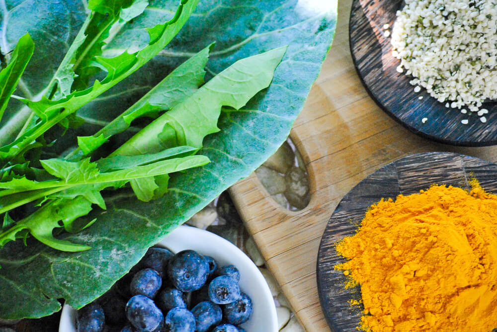 Health collage of leafy greens and super foods including collard greens, dandelion greens hemp seeds, antioxidant blueberries and anti-inflammatory turmeric on stones and a rustic wood cutting board