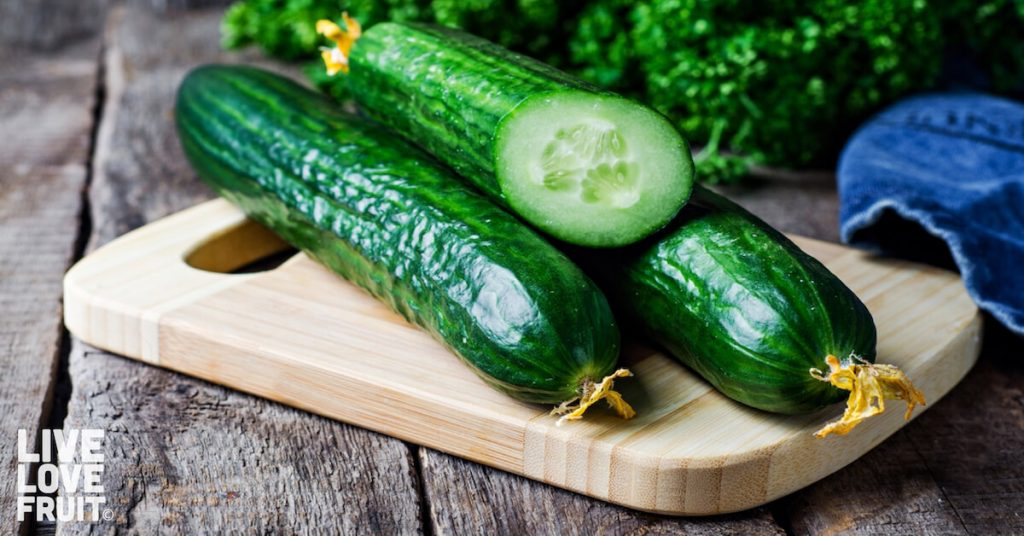 Fresh english cucumbers on a wooden board on rustic table with blue cloth