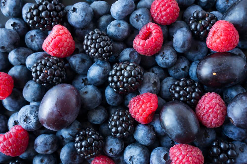 Background of fresh fruits and berries. Ripe blackberries, blueberries, plums, raspberries.