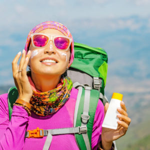 Hiker woman applying sunscreen with harmful ingredients