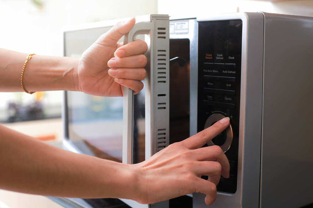 Woman's Hands Closing Microwave Oven Door And Preparing Food in microwave