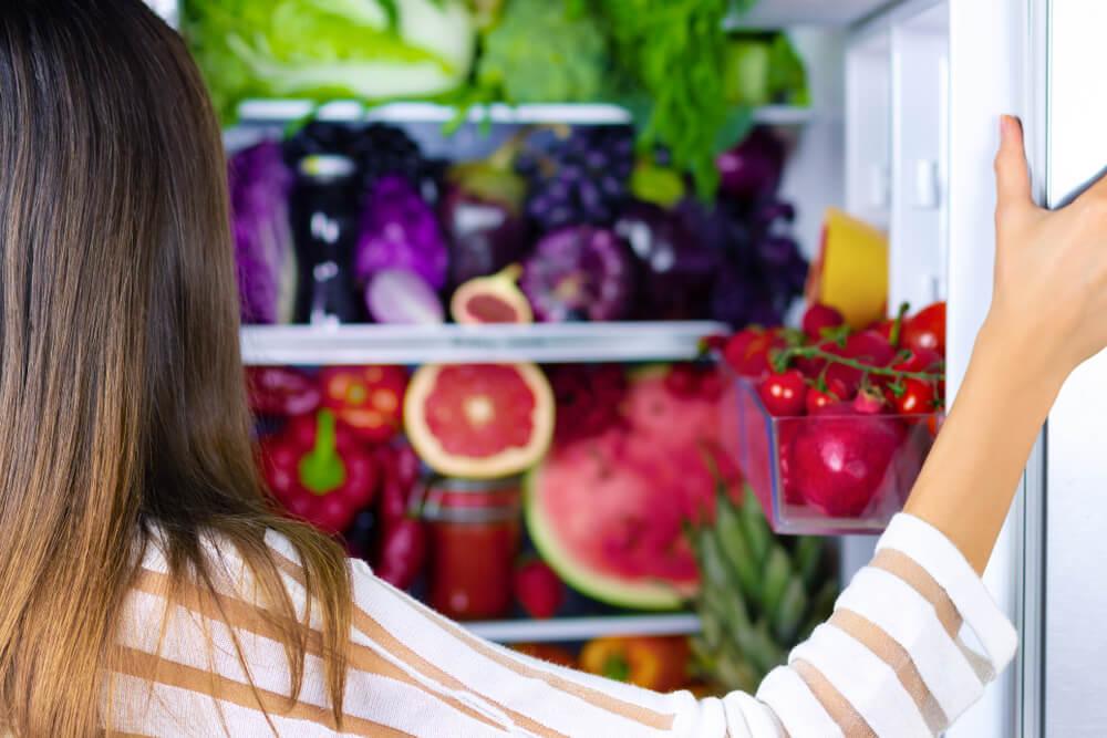 Vegan woman choosing healthy antioxidant colorful veggies, raw juice and fruits