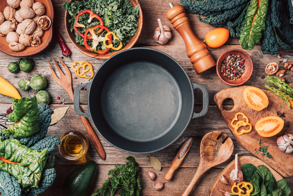 Various organic vegetables ingredients and empty iron cooking pot