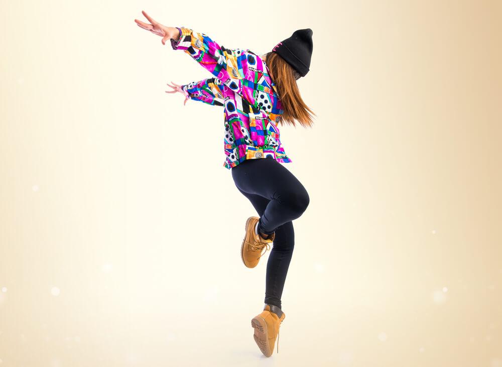 Young woman dancing street dance over ocher background