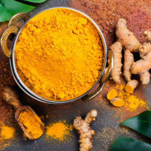 Turmeric powder and fresh root on grunge background