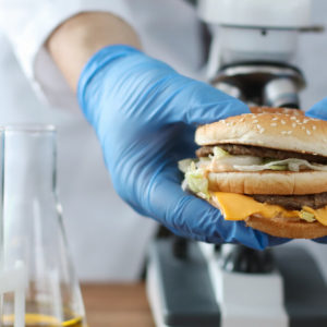 burger in hand with blue protective gloves closeup