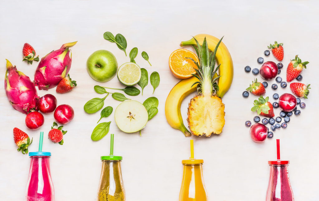 Bottles of Fruits smoothies with various ingredients on white wooden background