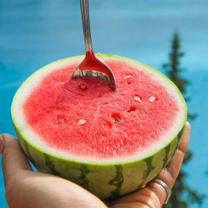 person holding watermelon with spoon in the fruit with backdrop of moraine lake