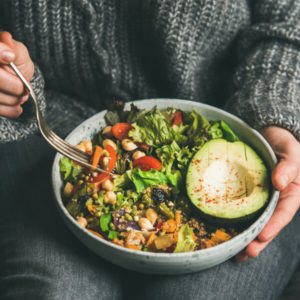 Woman in jeans and warm sweater holding bowl with fresh salad, avocado, beans, roasted vegetables, close-up