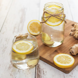 Ginger with lemon detox water in the morning on wooden background.