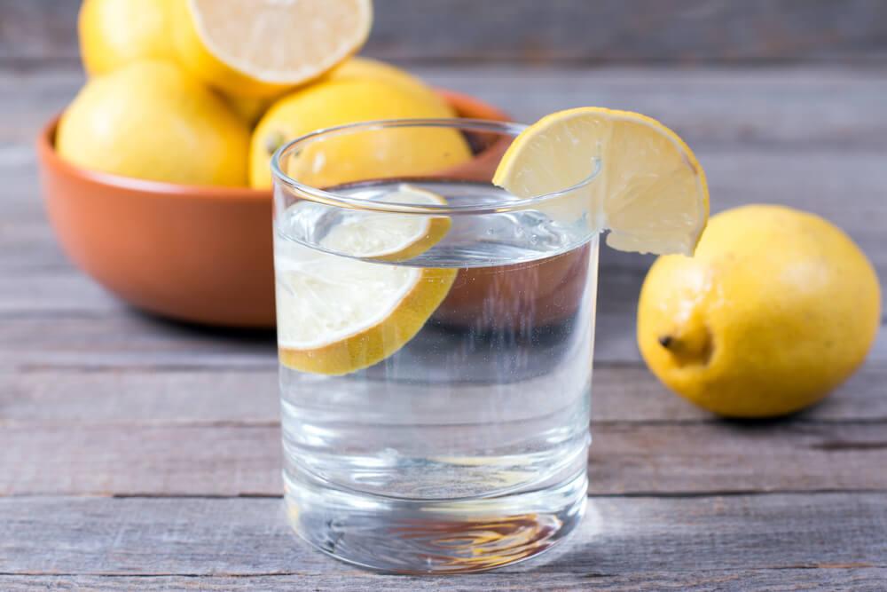 lemon water with bowl of lemons in back