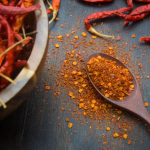 dried cayenne peppers with cayenne powder on wooden spoon