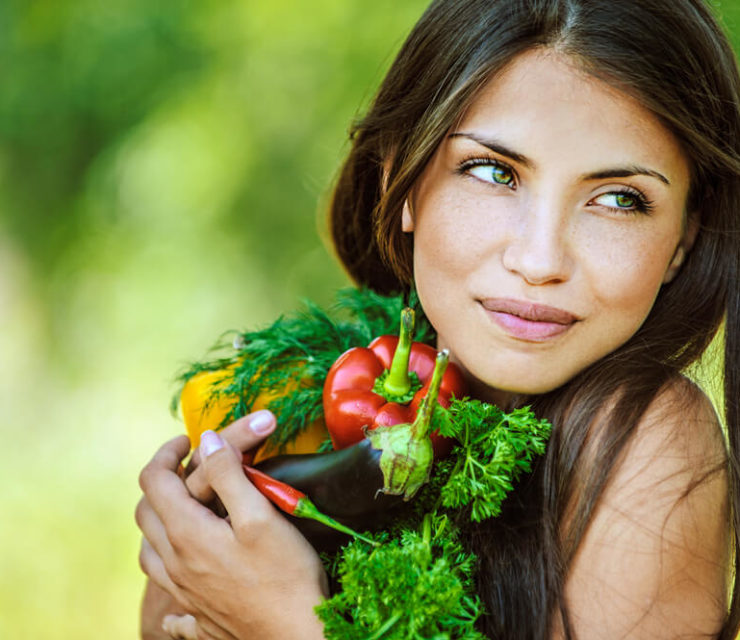 Portrait of young beautiful woman with bare shoulders holding vegetables