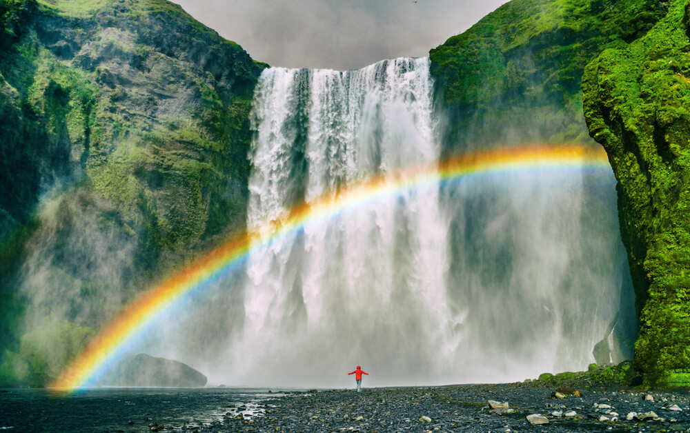 woman standing happily under a rainbow next to a waterfall