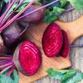 whole and cut beets on wooden cutting board with wooden background