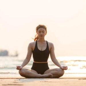 woman sitting on beach meditating
