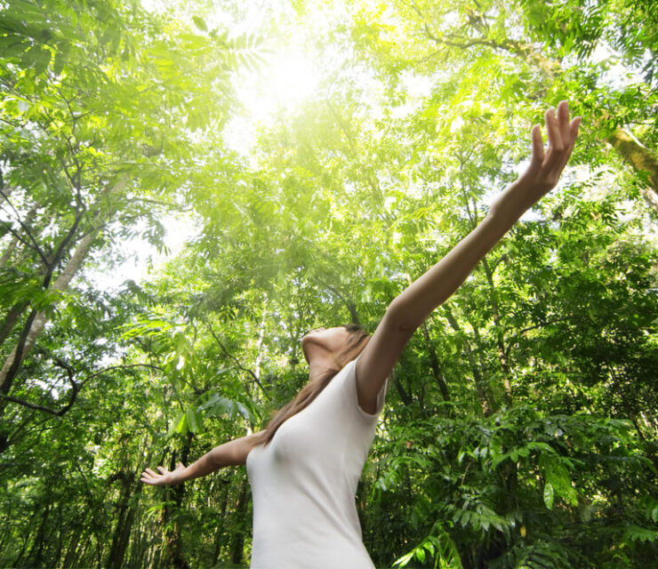 woman in forest with arms spread wide expressing happiness