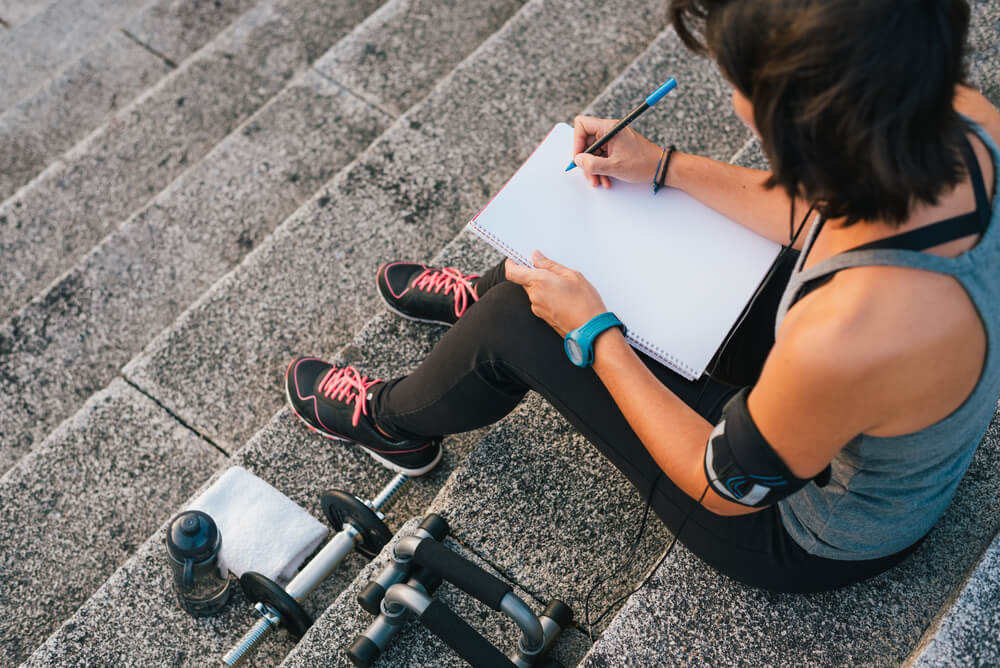 woman writing down fitness goals
