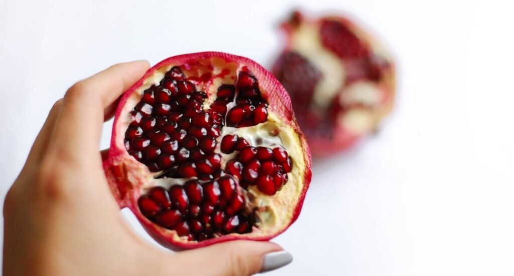 hand holding cut open pomegranate on white background