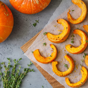 Baked pumpkin slices with thyme on a wooden board over grey table