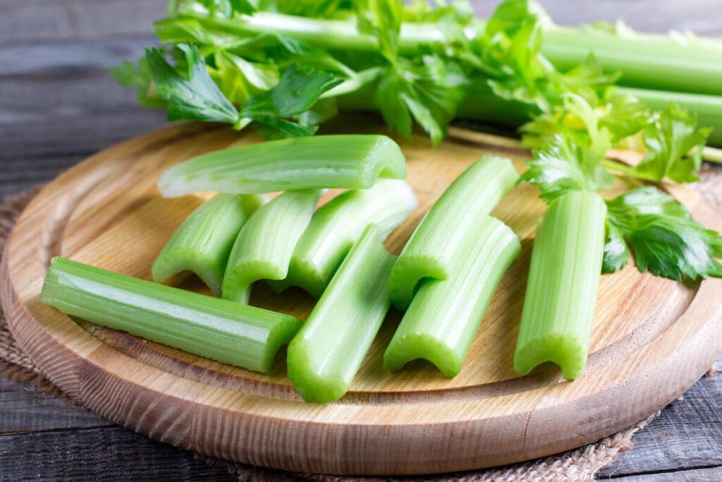 Fresh celery stems on wooden cutting board
