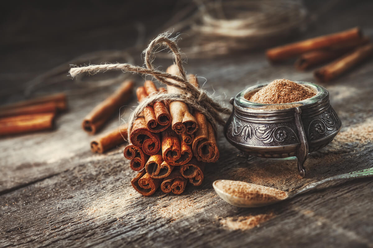 cinnamon sticks wrapped together with string on wooden table next to a small pot and spoon of cinnamon powder