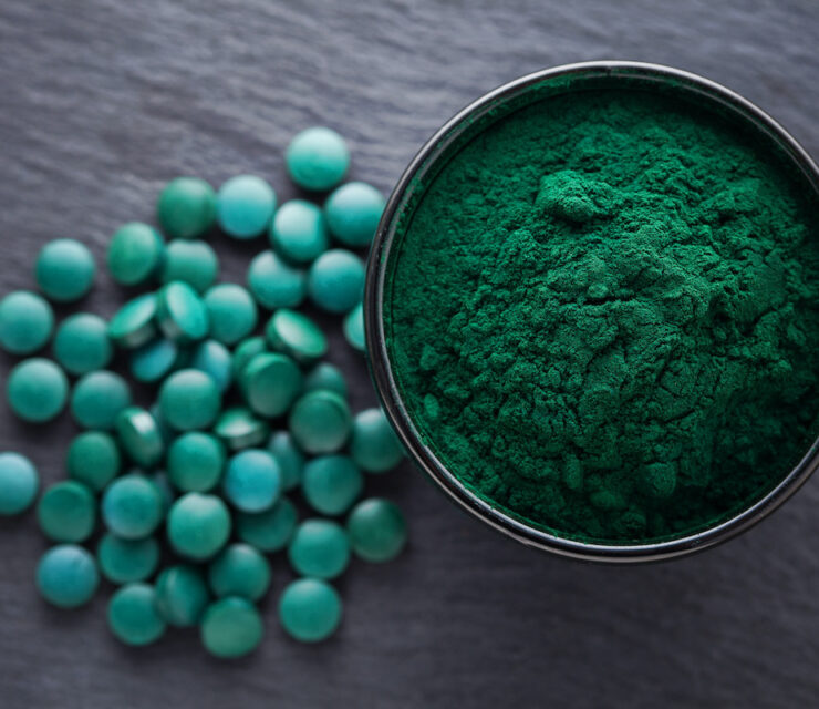 spirulina powder and tablets on wooden table