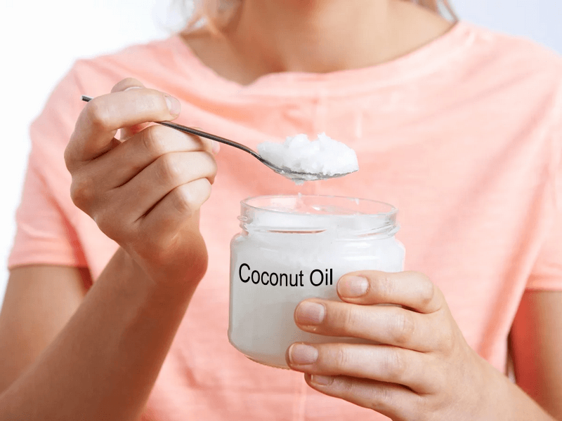A girl scooping a spoonful of solid coconut oil out of jar