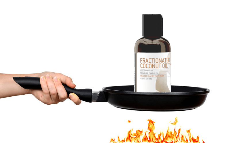 A bottle of fractionated coconut oil on a pan that's placed over a fire