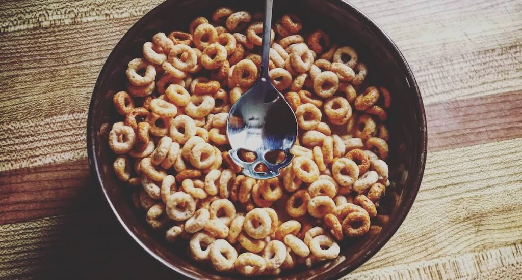 bowl of cheerios with skull-engraved spoon resting on top