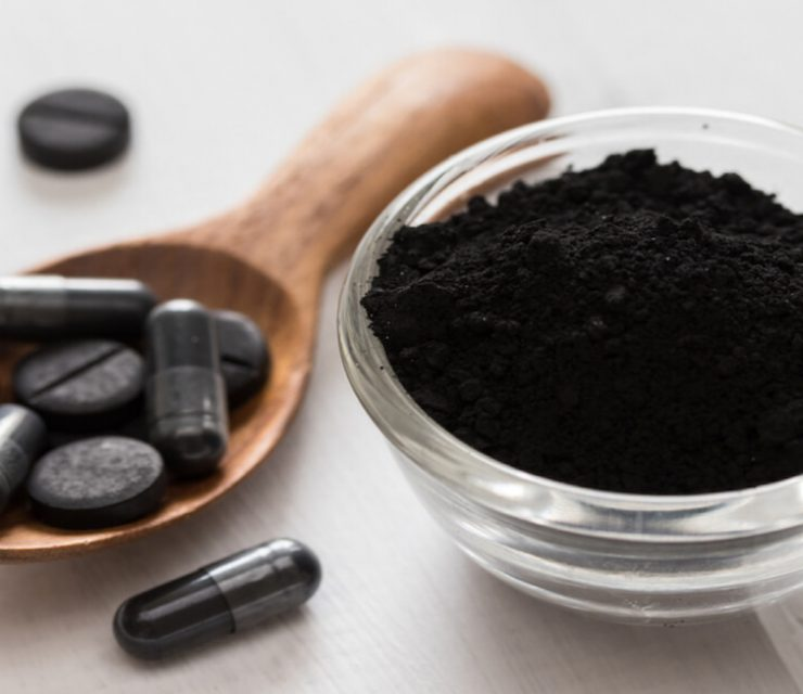 capsules and tablets of activated charcoal on a wooden spoon and table with a small glass cup of powdered activated charcoal beside