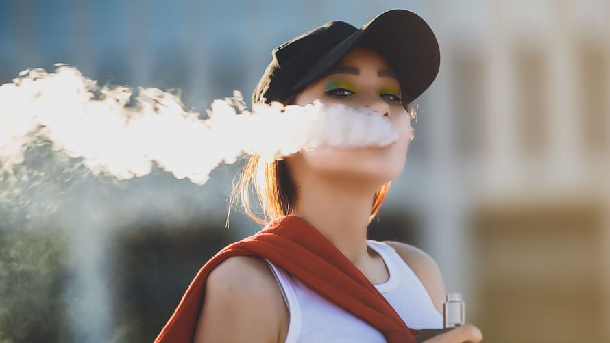 dangers of vaping demonstrated by girl with black hat and makeup blowing out vapour after vaping