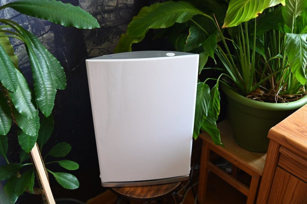 Compact air filtration device by Intellipure sitting on a wooden table surrounded by plants