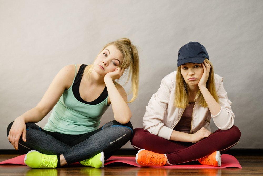 women looking bored and unmotivated to work out, trying to find excuses for not exercising