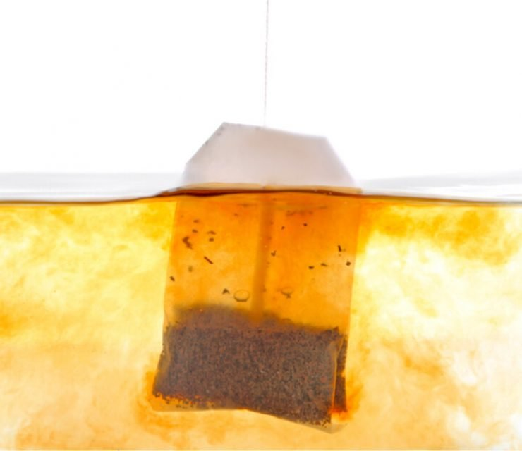 plastic tea bag steeping in water white background