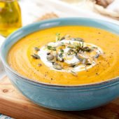 bowl of cream of pumpkin soup with pumpkin seeds on top