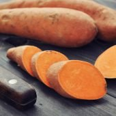 sweet potato on wooden platform with cut slices of sweet potato