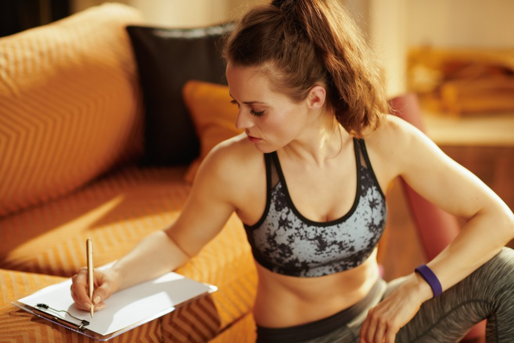 Woman writing down notes in workout gear, trying to stay fit during the holidays