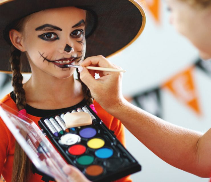 adult woman applying halloween makeup to little girl dressed as a witch