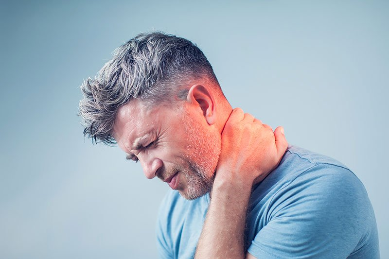 man holding neck after whiplash injury