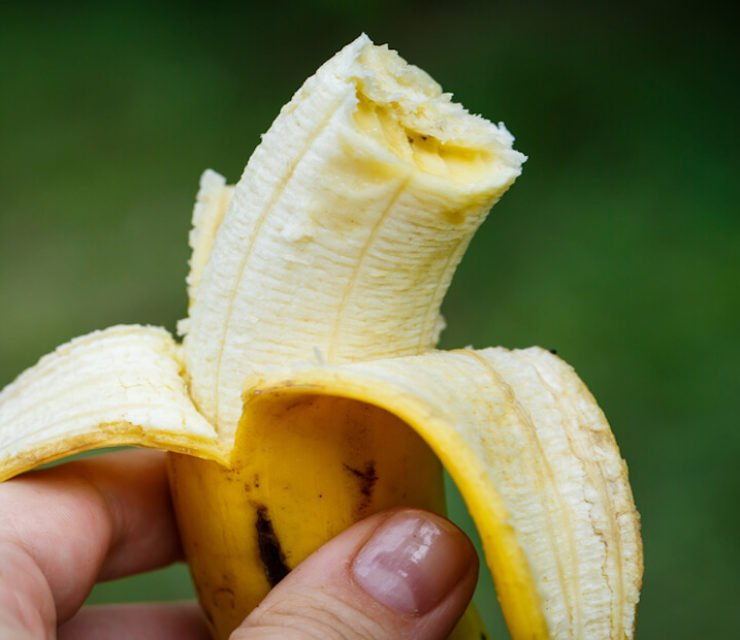person holding half-eaten banana against green background