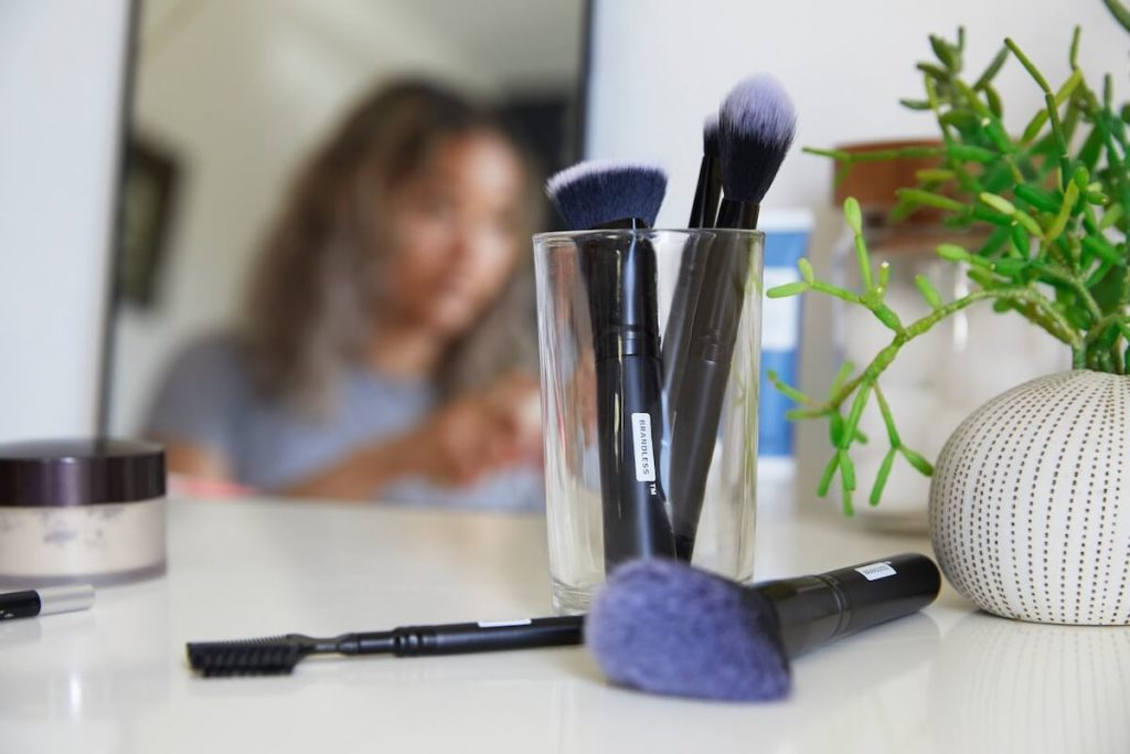 makeup brushes on desk with girl in background