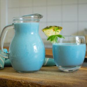 blauer Spirulina Smoothie mit Ananas auf Holztisch