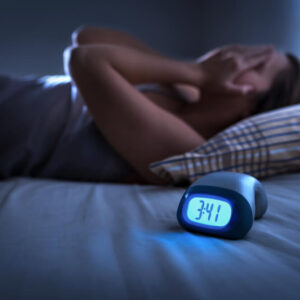 woman with hands on face next to alarm clock